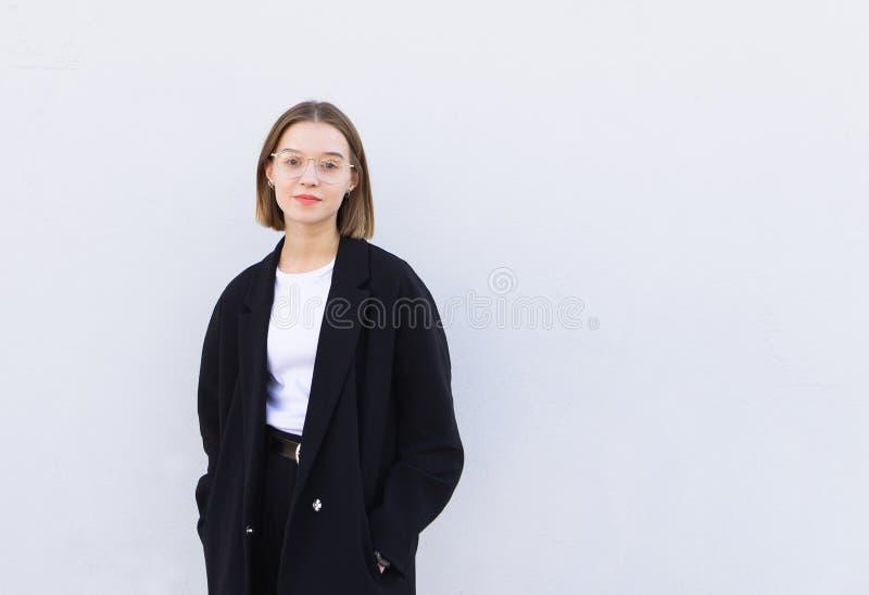 Retrato de un oficinista de sexo femenino joven elegante en lentes y una chaqueta, colocándose en un fondo blanco fotos de archivo