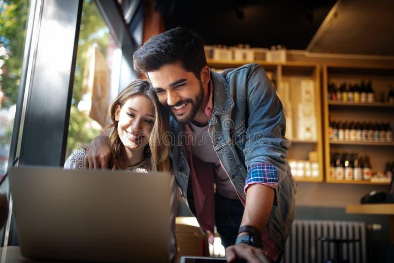 Retrato de un par alegre que hace compras en línea con el ordenador portátil fotos de archivo libres de regalías