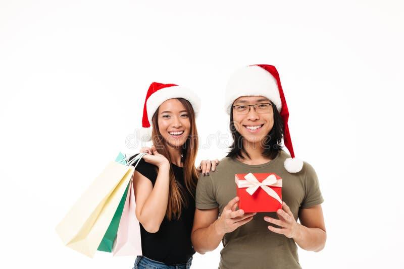 Retrato de un par asiático sonriente en sombreros de la Navidad foto de archivo libre de regalías