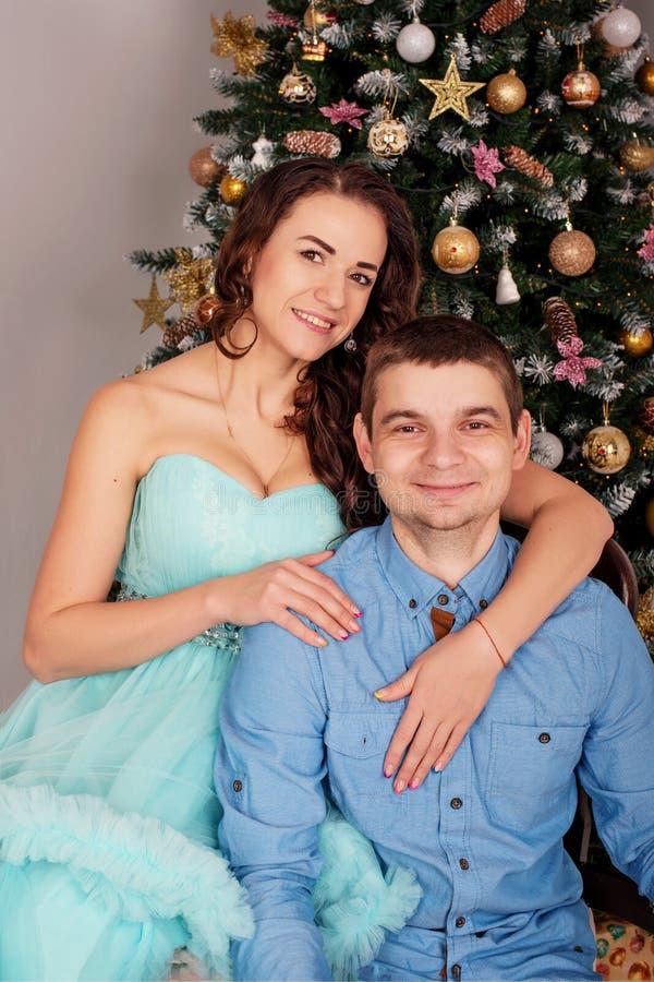Retrato de un par atractivo joven de la familia que abraza cerca de un árbol de navidad imagenes de archivo