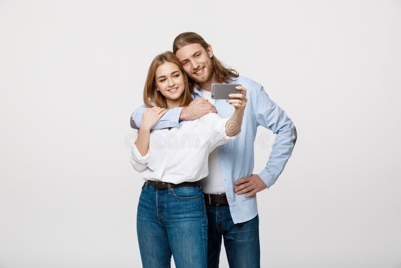Retrato de un par feliz que hace la foto del selfie con smartphone sobre el fondo blanco del estudio fotografía de archivo