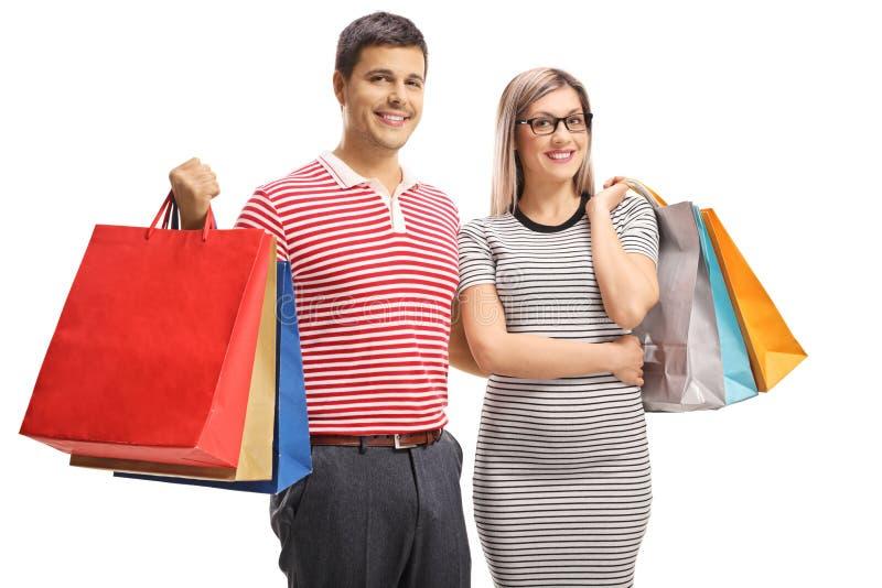 Retrato de un par joven alegre que presenta con los bolsos de compras imagenes de archivo