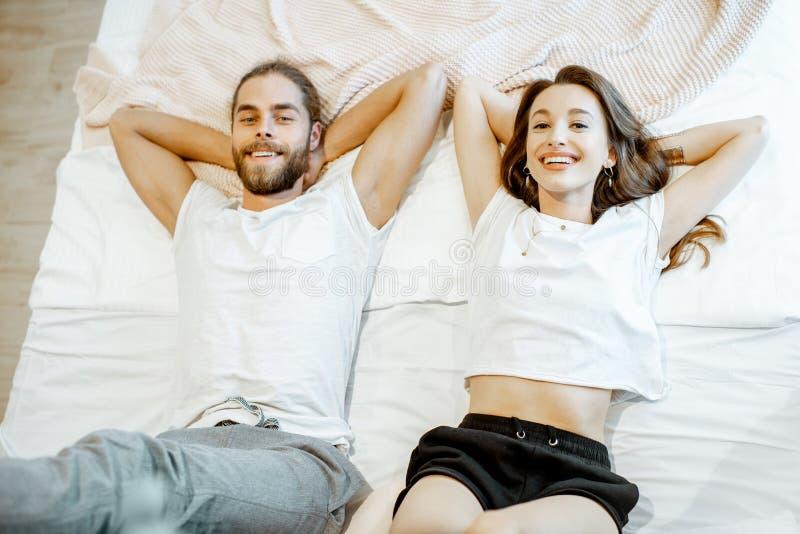Retrato de un par joven en la cama fotografía de archivo libre de regalías