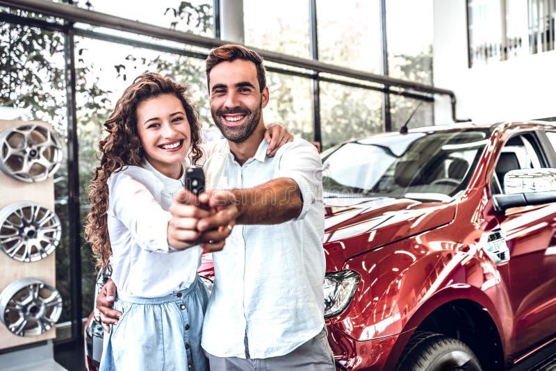 Retrato de un par joven feliz que abraza en llaves del coche del salón de un coche de la demostración a un vehículo nuevamente co foto de archivo