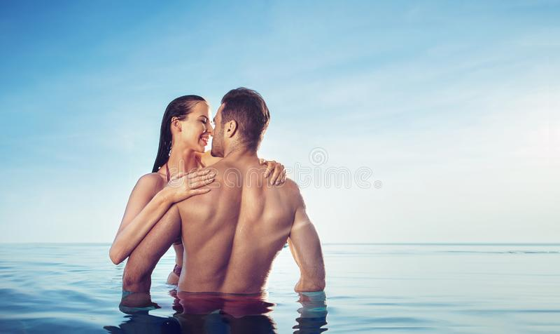 Retrato de un par joven, sensual que se relaja en una piscina tropical fotos de archivo