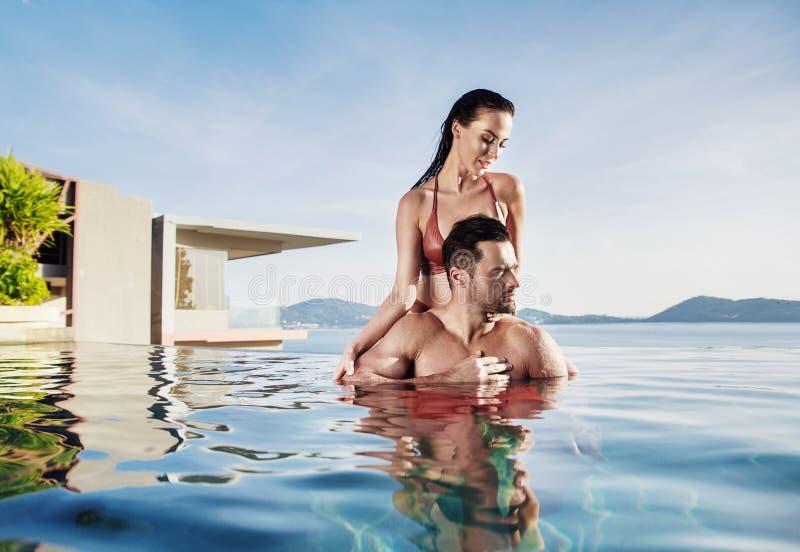 Retrato de un par joven, sensual que se relaja en una piscina tropical fotografía de archivo