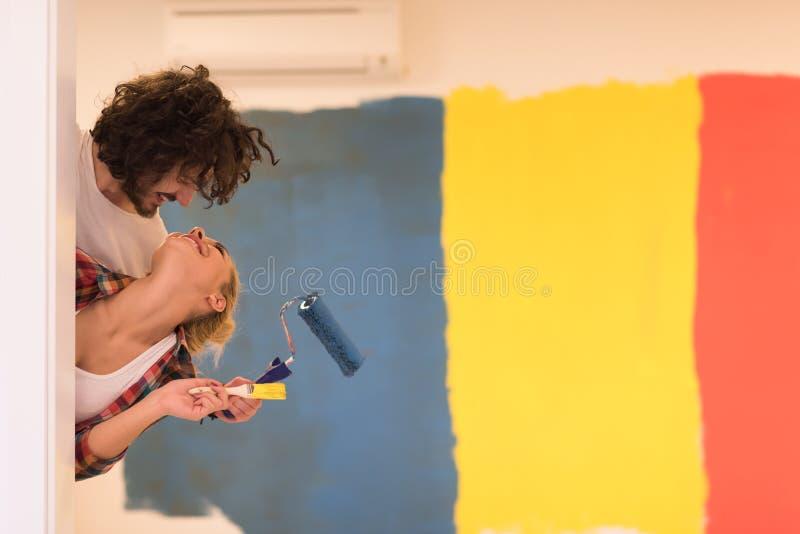 Retrato de un par que pinta la pared interior imágenes de archivo libres de regalías