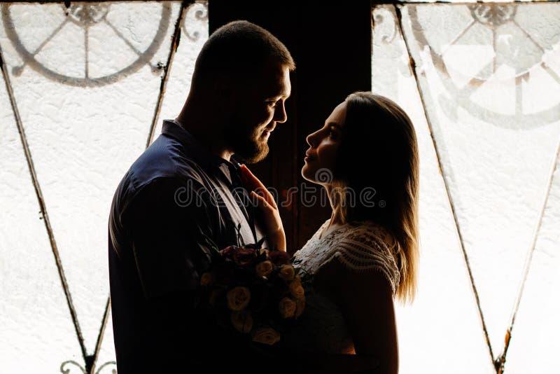 Retrato de un par romántico en un contraluz de una ventana o de una puerta, silueta de un par en una entrada con un contraluz, pa fotos de archivo libres de regalías