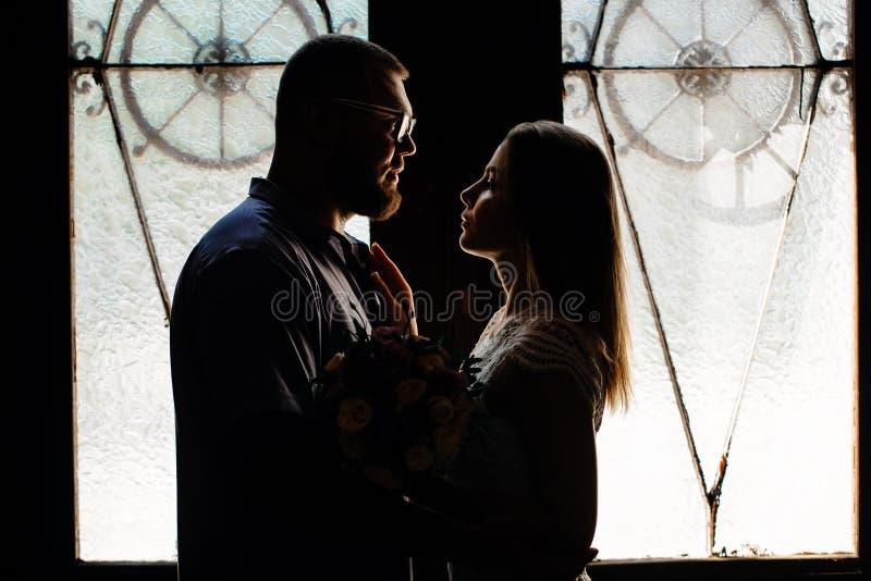 Retrato de un par romántico en un contraluz de una ventana o de una puerta, silueta de un par en una entrada con un contraluz, pa imagen de archivo