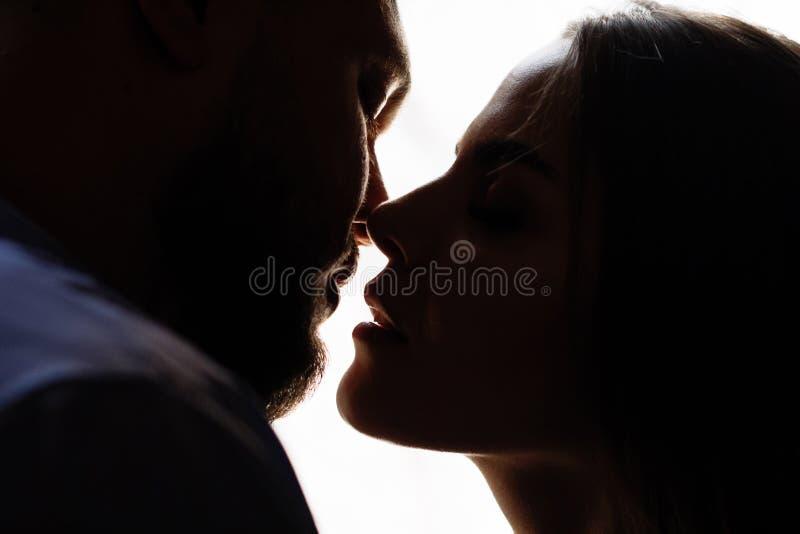 Retrato de un par romántico en un contraluz de una ventana o de una puerta, silueta de un par en una entrada con un contraluz, pa fotografía de archivo