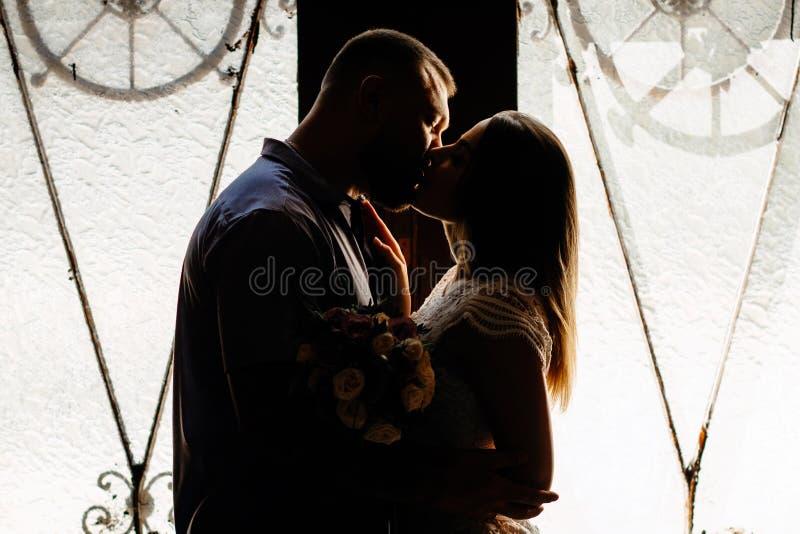 Retrato de un par romántico en un contraluz de una ventana o de una puerta, silueta de un par en una entrada con un contraluz, pa imágenes de archivo libres de regalías