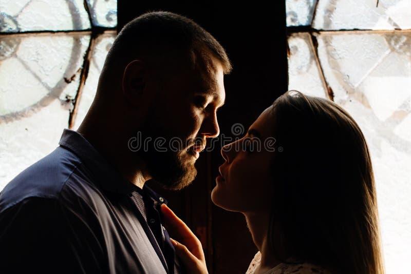 Retrato de un par romántico en un contraluz de una ventana o de una puerta, silueta de un par en una entrada con un contraluz, pa fotografía de archivo libre de regalías