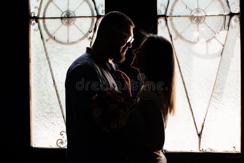 Retrato de un par romántico en un contraluz de una ventana o de una puerta, silueta de un par en una entrada con un contraluz, pa imagen de archivo libre de regalías
