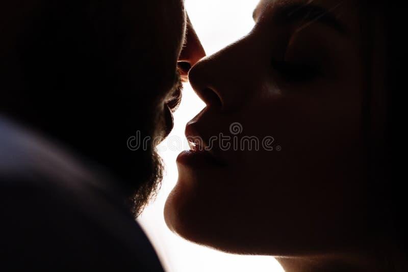 Retrato de un par romántico en un contraluz de una ventana o de una puerta, silueta de un par en una entrada con un contraluz, pa foto de archivo libre de regalías