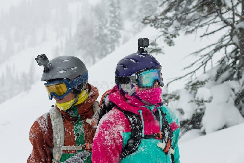 Retrato de un par de snowboarders que llevan cascos en la nieve que mira en diversas direcciones foto de archivo libre de regalías