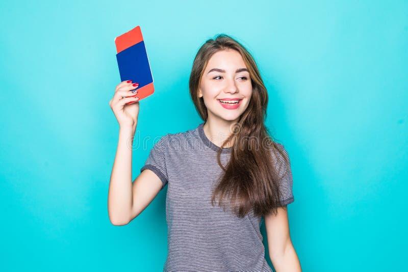 Retrato de un pasaporte sonriente feliz de la tenencia de la chica joven y de boletos que viajan sobre fondo azul imagen de archivo