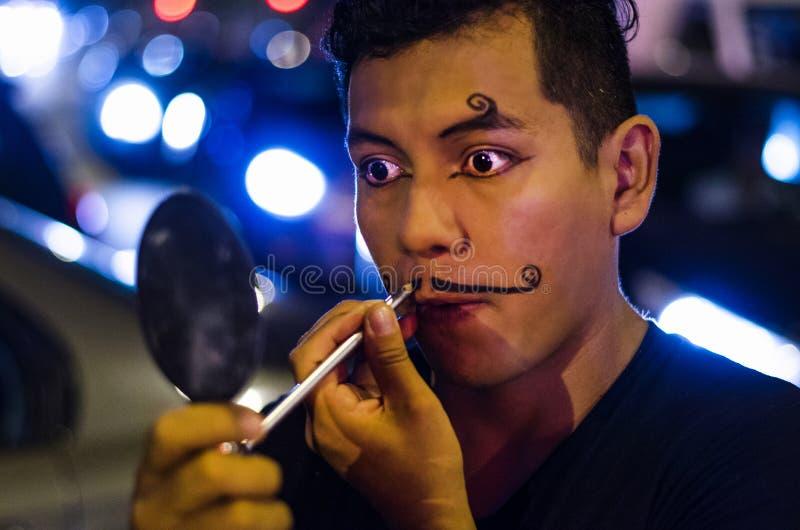 Retrato de un payaso joven que pone en los bigotes con maquillaje fotos de archivo