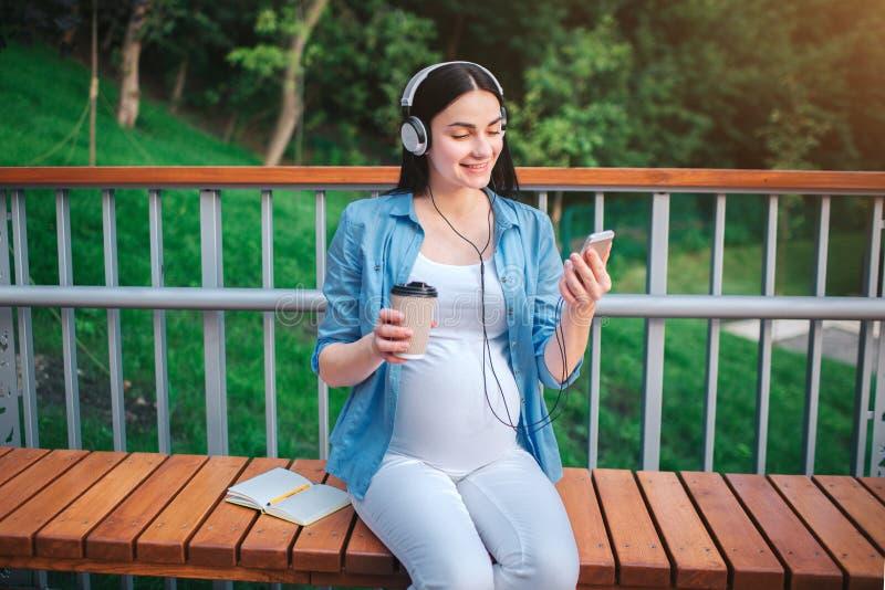Retrato de un pelo negro feliz y de una mujer embarazada orgullosa en una ciudad en el fondo Ella se está sentando en un banco de fotos de archivo