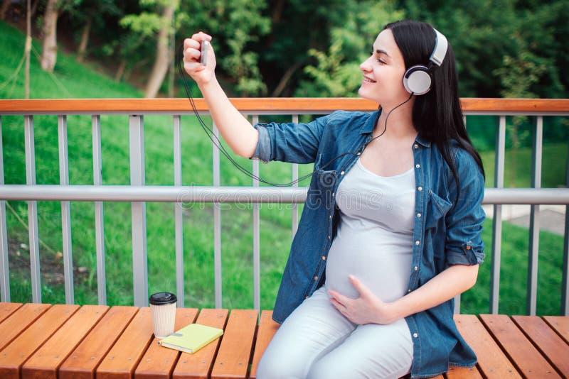 Retrato de un pelo negro feliz y de una mujer embarazada orgullosa en una ciudad en el fondo Ella se está sentando en un banco de imagenes de archivo