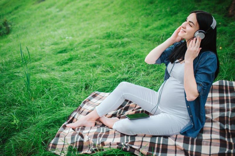 Retrato de un pelo negro feliz y de una mujer embarazada orgullosa en una ciudad en el fondo Ella se está sentando en un banco de foto de archivo libre de regalías
