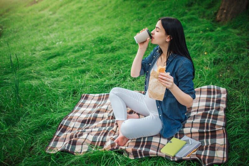 Retrato de un pelo negro feliz y de una mujer embarazada orgullosa en una ciudad en el parque Foto del modelo femenino que toca s imágenes de archivo libres de regalías