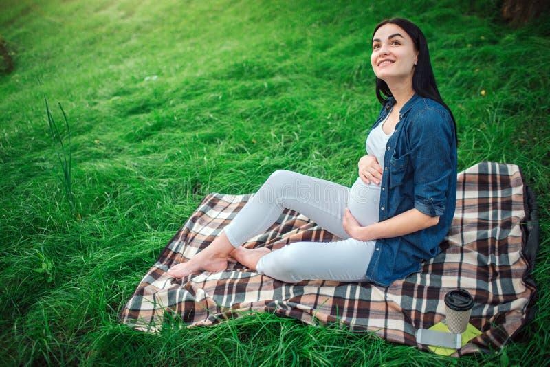 Retrato de un pelo negro feliz y de una mujer embarazada orgullosa en una ciudad en el parque Foto del modelo femenino que toca s foto de archivo libre de regalías