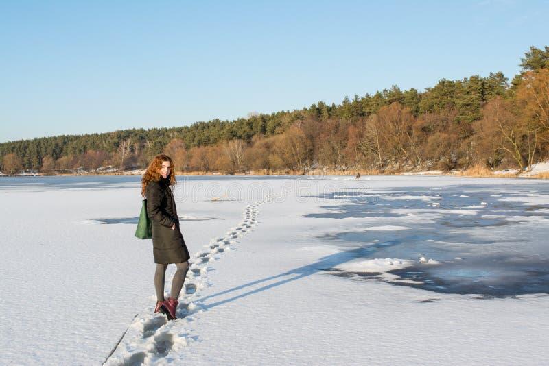 Retrato de un pelo rojo hermoso joven que cruza el río congelado cerca de bosque foto de archivo libre de regalías