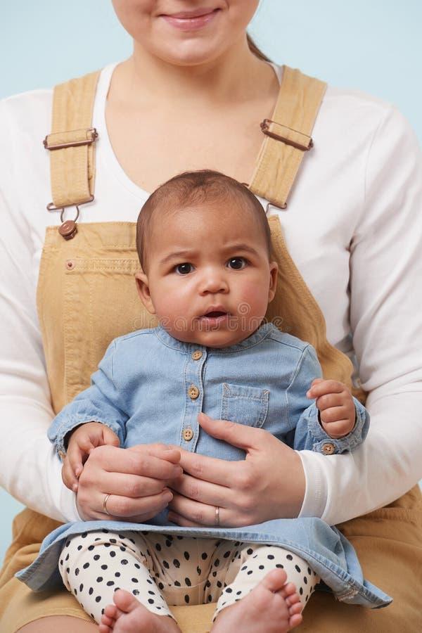Retrato de un pequeño bebé en los brazos de su madre contra fondo azul claro fotos de archivo