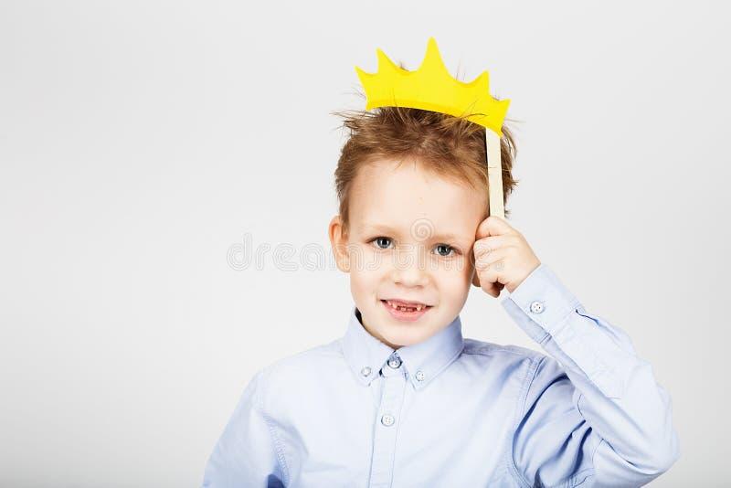 Retrato de un pequeño escolar lindo con aga de papel amarillo de la corona fotos de archivo