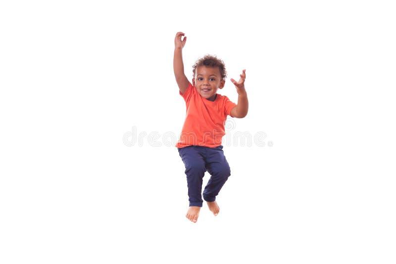 Retrato de un pequeño muchacho afroamericano lindo que salta en una tranvía imagen de archivo