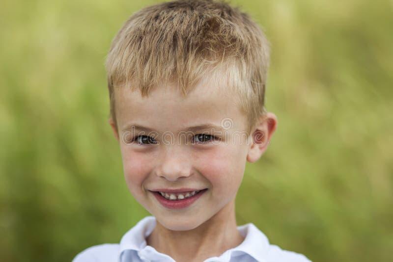 Retrato de un pequeño muchacho sonriente con el pelo rubio de oro i de la paja imagen de archivo