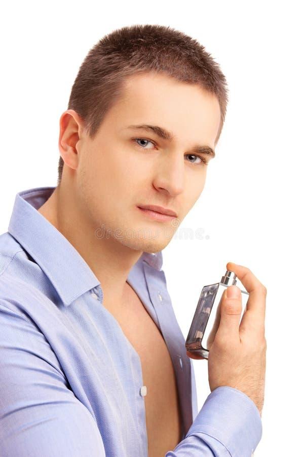 Retrato de un perfume de rociadura atractivo, hermoso del hombre joven fotografía de archivo libre de regalías