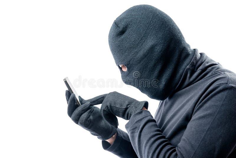 Retrato de un pirata informático con un teléfono móvil robado en un blanco fotos de archivo