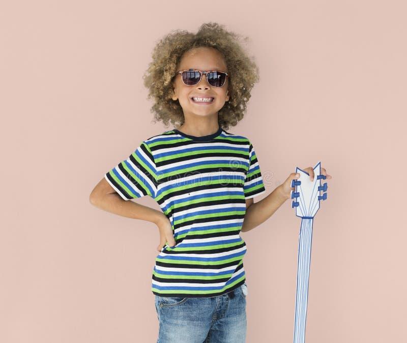 Retrato de un poco muchacho de la ascendencia africana con una guitarra aislada foto de archivo