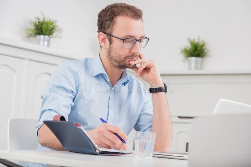 Retrato de un profesional joven en el escritorio en la oficina fotos de archivo