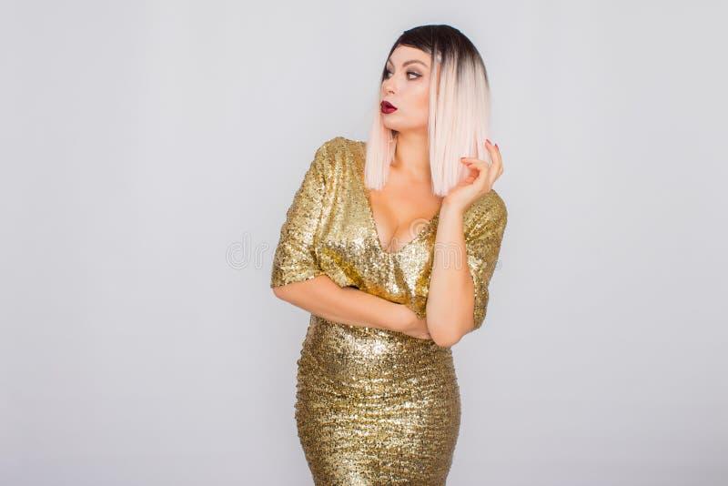 Retrato de un rubio hermoso con maquillaje brillante en un vestido del oro fotos de archivo