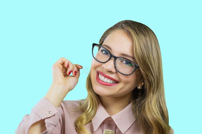 Retrato de un rubio joven atractivo en los vidrios que llevan a cabo su mano a ella que mira la cámara con una sonrisa amplia en imagen de archivo