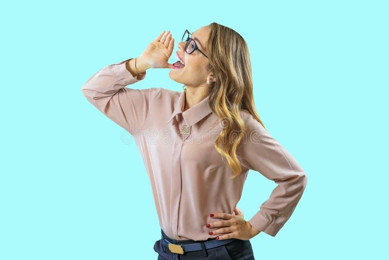 Retrato de un rubio rizado joven en vidrios que grita llevando a cabo una mano a su boca que mira al lado en un azul imágenes de archivo libres de regalías