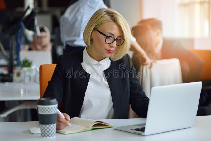 Retrato de un socio comercial femenino rubio en su 30 ` s que se sienta en su escritorio ordenado delante de su ordenador imagen de archivo libre de regalías