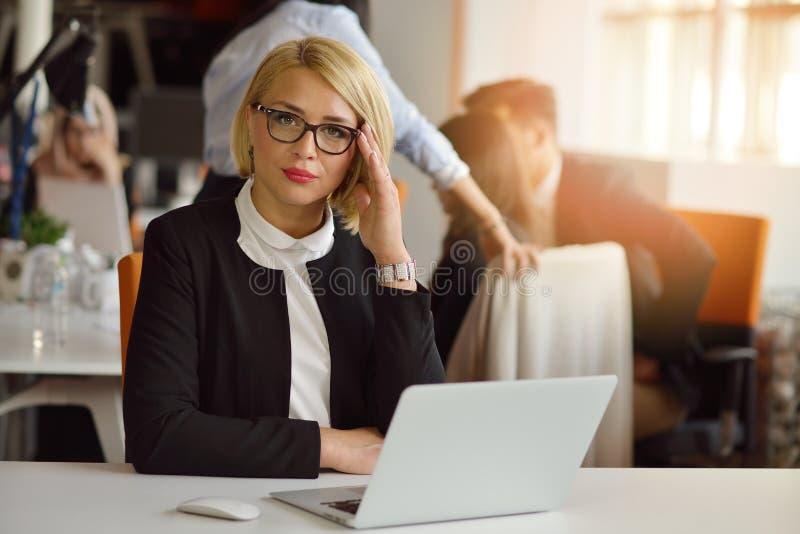 Retrato de un socio comercial femenino rubio en su 30 ` s que se sienta en su escritorio ordenado delante de su ordenador fotos de archivo