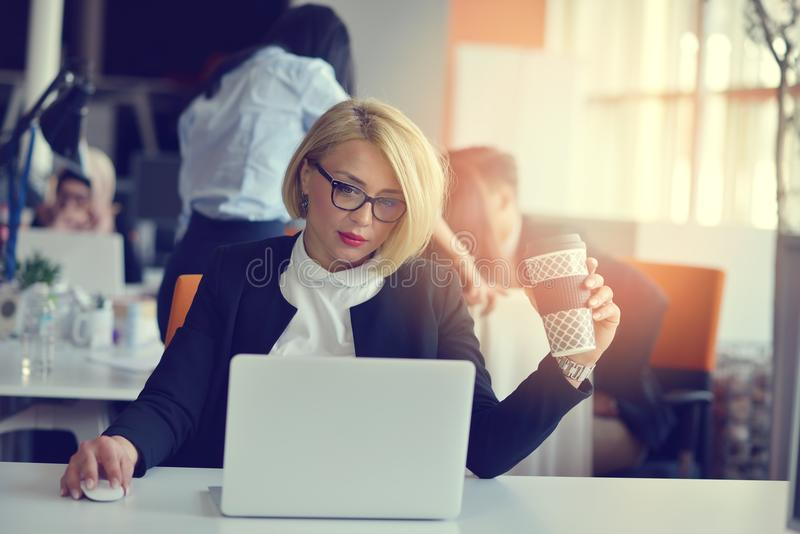 Retrato de un socio comercial femenino rubio en su 30 ` s que se sienta en su escritorio ordenado delante de su ordenador imagenes de archivo