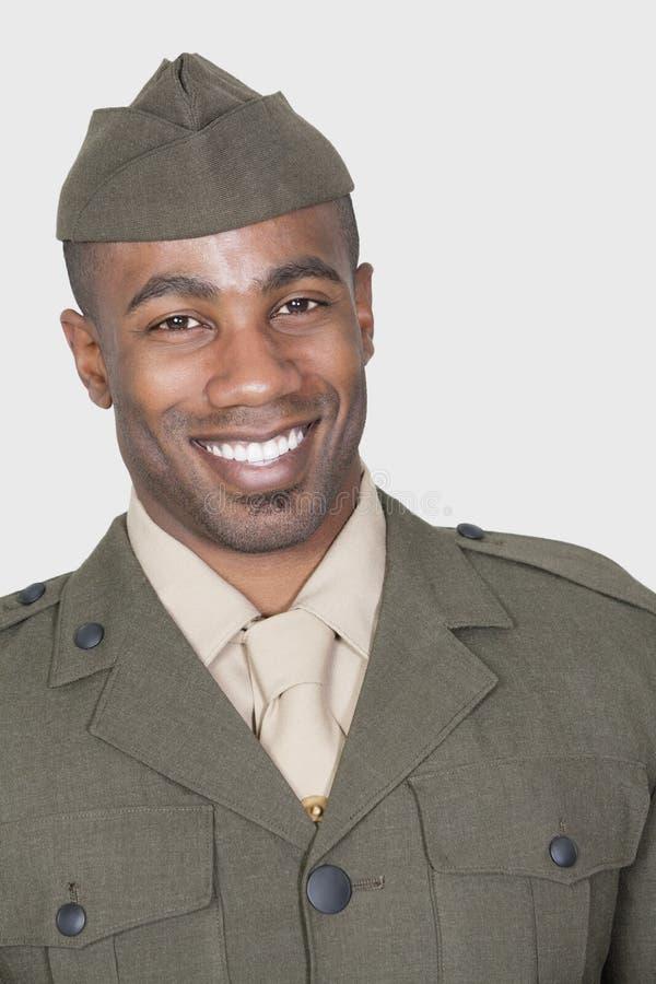 Retrato de un soldado de sexo masculino de los E.E.U.U. del afroamericano que sonríe sobre fondo gris fotografía de archivo libre de regalías