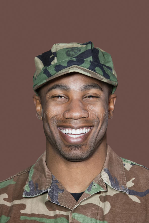 Retrato de un soldado joven alegre de los E.E.U.U. Marine Corps del afroamericano sobre fondo marrón foto de archivo libre de regalías