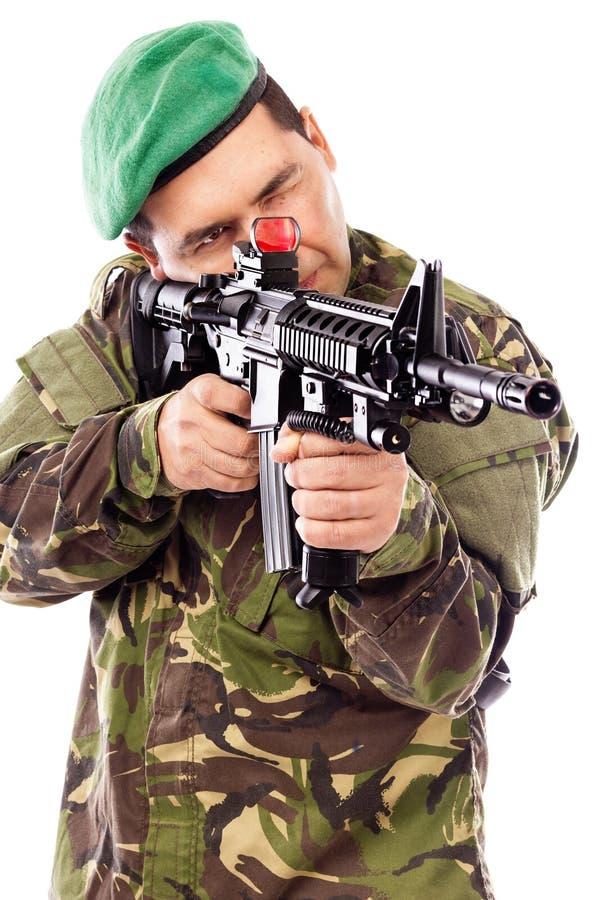 Retrato de un soldado joven que apunta con un arma fotos de archivo