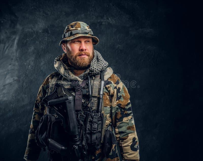 Retrato de un soldado de las fuerzas especiales en el uniforme camuflado militar, mirando de lado fotos de archivo