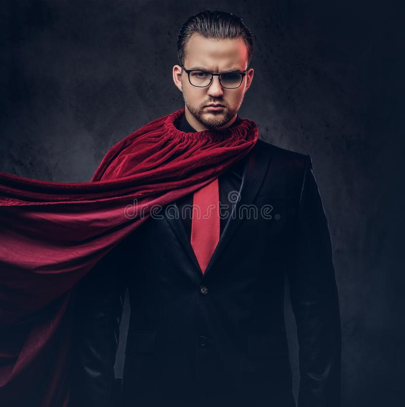 Retrato de un super héroe del genio en un traje negro con un lazo rojo en un fondo oscuro imagen de archivo libre de regalías