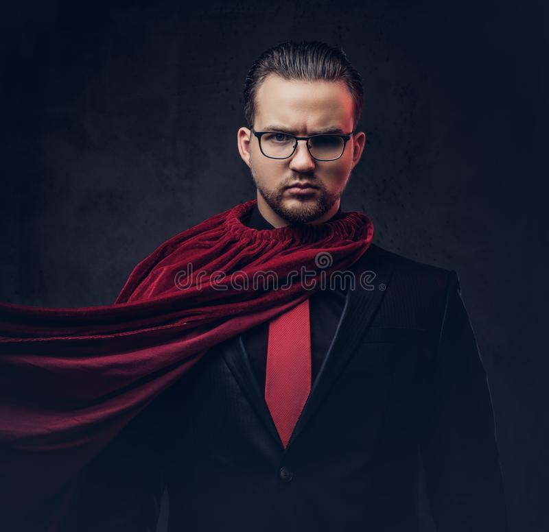 Retrato de un super héroe del genio en un traje negro con un lazo rojo en un fondo oscuro foto de archivo libre de regalías