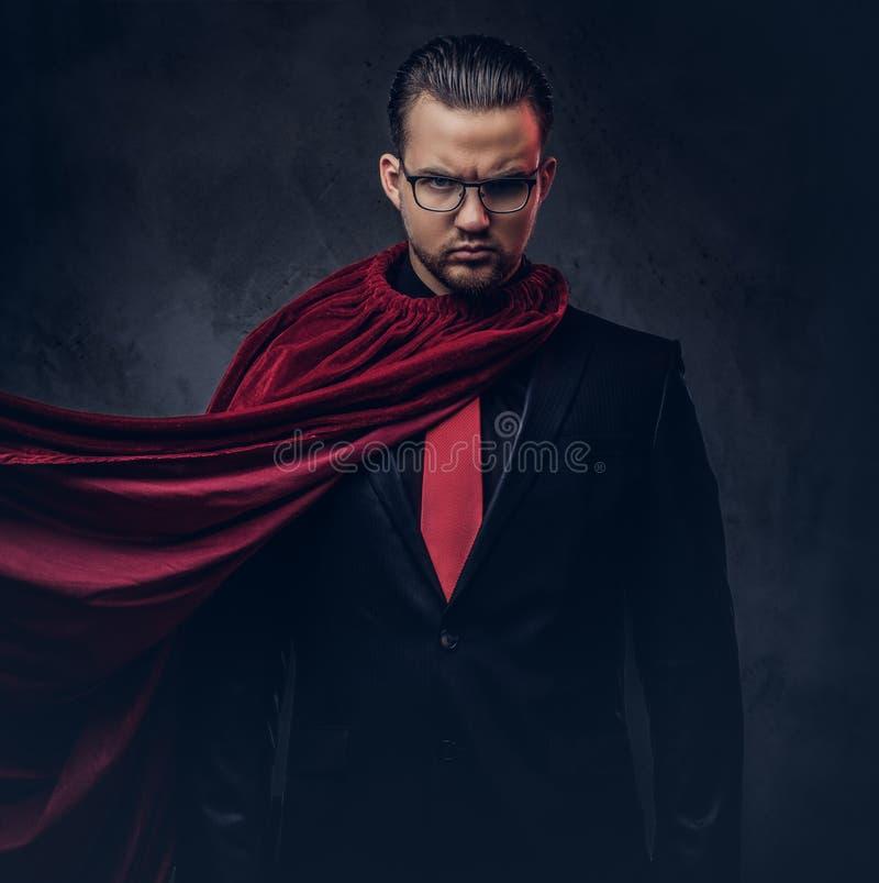 Retrato de un super héroe del genio en un traje negro con un lazo rojo en un fondo oscuro imagenes de archivo