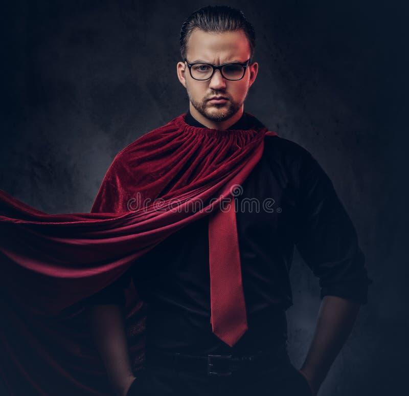 Retrato de un super héroe del malvado del genio en una camisa negra con un lazo rojo foto de archivo libre de regalías