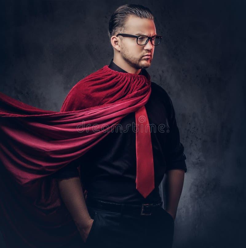 Retrato de un super héroe del malvado del genio en una camisa negra con un lazo rojo imagenes de archivo
